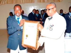 Azize Bamogo recevant la charte du Lions Club Ouagadougou Pacifique des mains du Gouverneur TOUNKARA